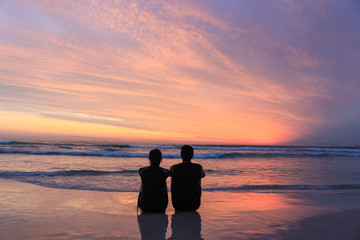 couple at the beach watching the sunset