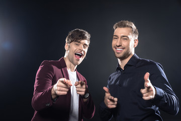 handsome young men in stylish clothes pointing at camera on black