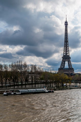 A bateau-mouche on the Seine near the Eiffel Tower on a day with dramatic sky, Paris, France