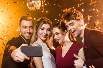 group of happy friends taking selfie with smartphone during party