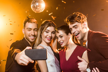 group of smiling friends taking selfie with smartphone during party