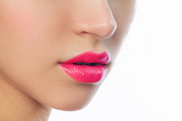 Close-up of beautiful lips with pink lipstick. The perfect contour of the lips and a clean tonal makeup base create a fashionable, well-groomed makeup result. Spa treatments and cosmetology injections