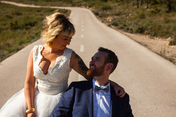 Newlywed couple pose in the middle of a lonely road
