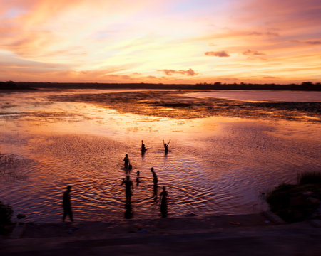 People in water at sunset