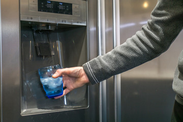 Male hand is pouring cold water and ice cubes from dispenser of home fridge.