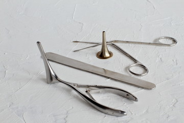 Rare old medical steel instruments for examination and treatment of the ear, throat, nose on white concrete background. Retro. Black and white photography.