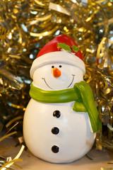 Figurine de bonhomme de neige devant une guirlande