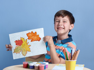 Happy smiling European boy demonstrating picture he has painted at home.