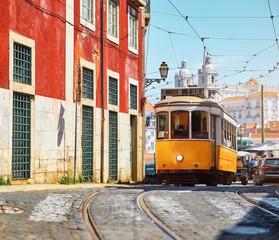 Lisbon, Portugal. Vintage yellow retro tram on narrow bystreet