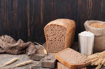 Wholegrain bread. Unleavened wheat  bread on a cutting board with flour, wheat grains, spikelets on a wooden brown table. A loaf of bread cutted into pieces. Copy space. Dark background. Homemade.