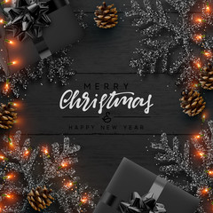 Christmas composition on wooden background. Xmas decoration design, box gift, snowflake color black, gold light garland, pine cone. Wood texture. Flat lay, top view.