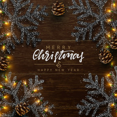Christmas composition on wooden background. Xmas decoration design, snowflake color black, gold light garland, pine cone. Brown realistic Wood texture. Flat lay, top view.