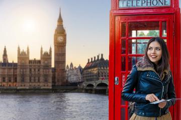 Weibliche Touristin in London vor einer roten Telefonzelle schaut auf den Big Ben Turm und Westminster Palast beim Sightseeing