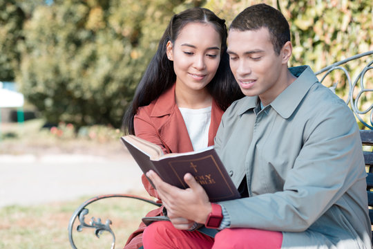 Cheerful loving couple reading religious literature together