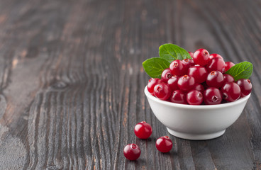 Cranberry. Cranberries with green leaves in small white bowl on the dark wooden table. Fresh cranberries. Copy space. Selective focus. Macro. Closeup.