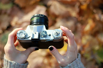 Vintage camera in hand on blurred background. Close-up, focus on camera controls