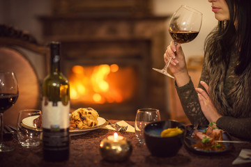 pretty woman drinking red wine and eating in restaurant, winter time, romantic dinner