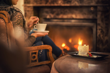woman seating near fireplace and drinking cup of coffee and eating beatiful winter dessert with chocolate, product photography for patisserie
