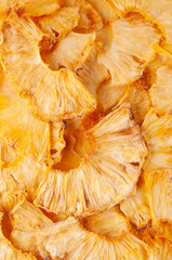 Dried pineapple slices (chips) background. Dehydrated crispy fruit slices. Heap, pile of sun dried crunchy pineapples.