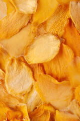 Dried mango slices (chips) background. Dehydrated crispy fruit slices, pieces. Heap of sun-dried mango fruit.