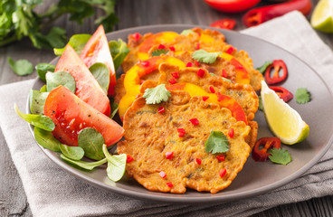 Indian chickpea crepes Pudla served on a plate with tomatoes, lime, cilantro, mash (mung bean) salad, chilli, ginger, bell pepper.