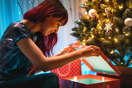Cheerful woman opening Christmas gift box under tree at home