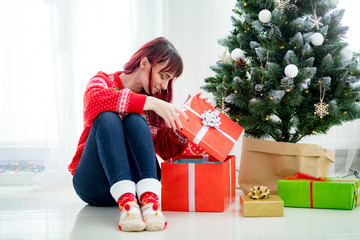 Smiling beautiful woman looking at gift boxes under christmas tree