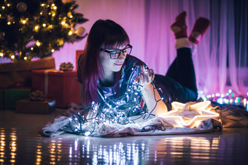 Young woman lying on floor surrounded by Christmas lights decorations at home