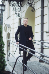 Young man in black outfit walks in old city.