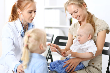 Doctor examining a little boy with stethoscope. Mother holds her son on her lap. Motherless and medicine concept