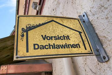 """Schild mit der Aufschrift """"vorsicht Dachlawinen"""" an einem Haus in Braunlage im Harz"""