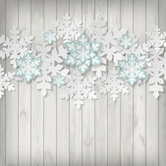 Paper snowflake on wooden background.