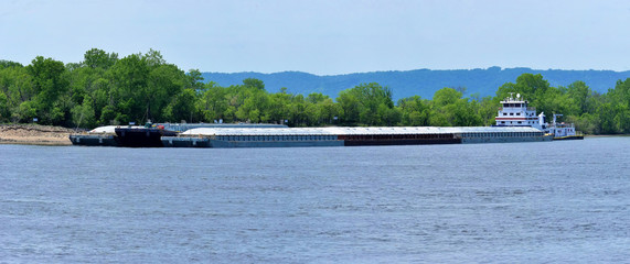 multiple barges being transported on the mississippi river
