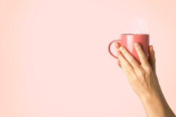 Female hand holding a purple cup with hot coffee or tea on a light pink background. Breakfast concept with hot coffee or tea