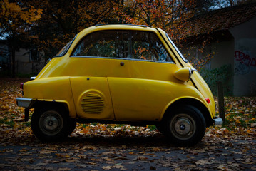 A tiny yellow old car car in autumn