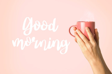 Female hand in clothes holding a purple cup with hot coffee or tea on a pink background. Added text Good morning. Breakfast concept with hot coffee or tea