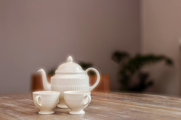 tea pot and cups on wooden table, still life in a home vintage design cute and cozy, space for text