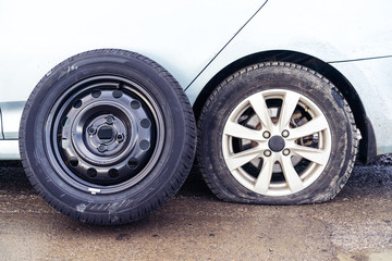 spare tire and flat tyre on roadon the background of the car. Car tire leak because of nail pounding. .