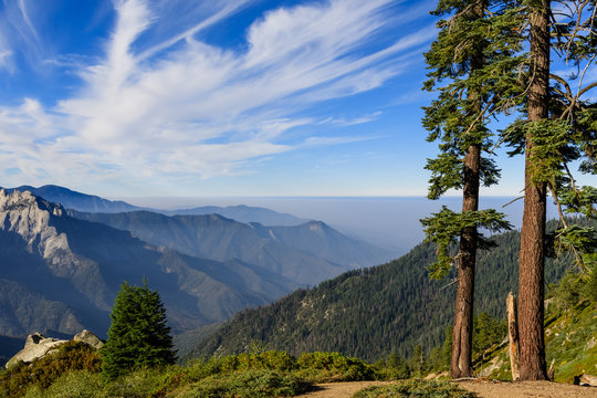 Landscape in Sequoia National Park in Sierra Nevada mountains on a sunny day; smoke from wildfires visible in the background, covering the valley;