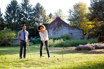 Couple enjoying croquet game on grassy field