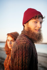 Portrait of couple standing at beach against sky