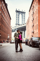 Couple kissing on cobbled street amidst buildings against Manhattan Bridge in city