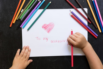 Kid's hands with pencil draws heart on white paper. Mother's day concept. Celebration. Hand made card. Top view. To my mummy words.