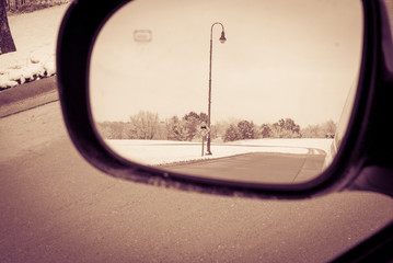 View from rear view mirror of road sign while driving