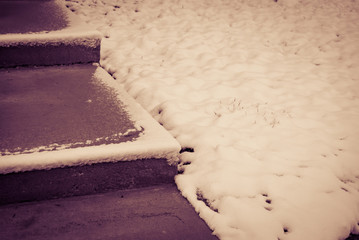 Snow covered ground and concrete steps