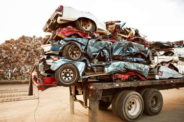 Stack of crushed cars on trailer at junkyard