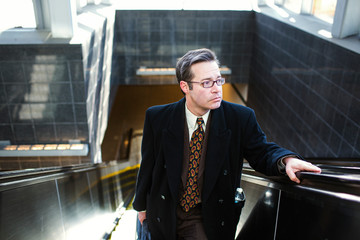 High angle view of man looking away while standing on escalator