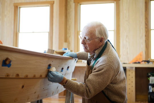 Side view of senior worker working on canoe in workshop