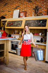 A beautiful blonde with buckets in her arms standing in the kitchen