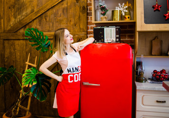The pretty girl in an apron is in the kitchen near the red refrigerator